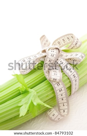 Celery with tape measure on the white background, concept of healthy nutrition and diet - stock photo