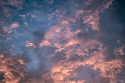 Celestial World concept. Dark purple blue pink natural bright sunset sky cumulus clouds. Background natural color of evening cloudscape panorama. Ideal for design wallpaper
