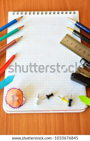 Cell notepad for writing with ring, compass, ruler, pins, color pencils, fountain ballpoint pen, black stapler, mark and shaving on wooden table in office