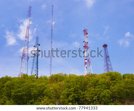 Cell phone and communication towers against blue sky with scattered clouds