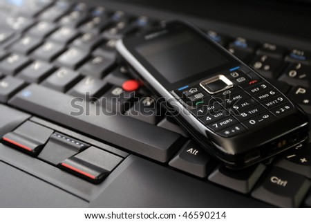 Cell phone(clean!) on laptop keyboard as a wireless technology concept. - stock photo