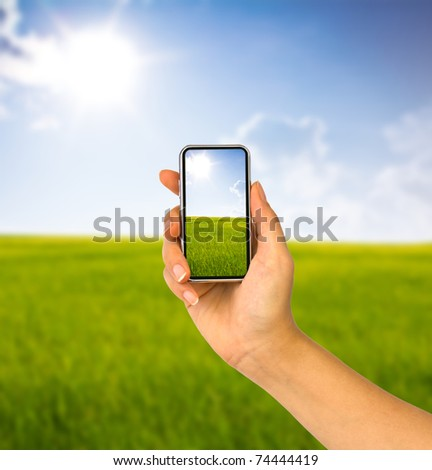 Cell phone in hand and country view of sunny day
