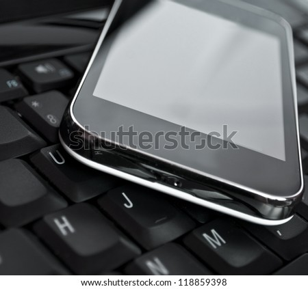 Cell phone on laptop keyboard - Business concept