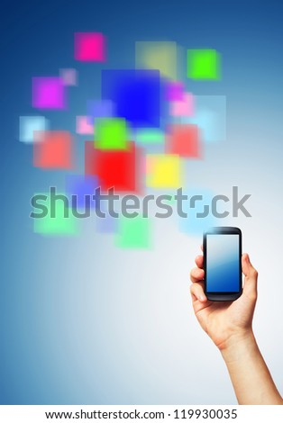 Cell phone (smartphone with touchscreen) in male hand and a futuristic digital depiction of social media over blue background