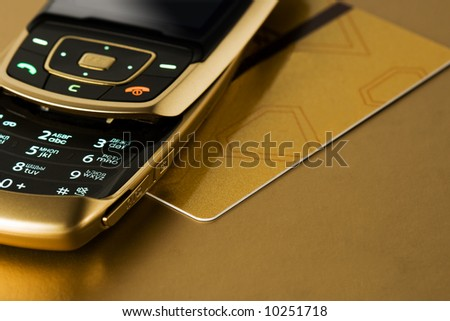 cell phone with gold credit card with gold background