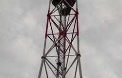 Cell tower maintenance staircase. Communications tower ladder.  Element of a metal tower. Staircase with safety guard. Robust construction for walking up. Tall structure. Danger of falling