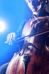 Cellist playing classical music on cello on black background