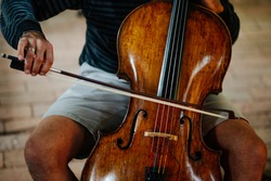 Cellist plays music on a cello with a bow. Shallow depth of field and selective sharpness