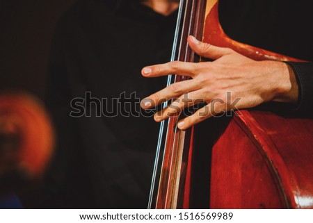 Cellist's fingers touch the cello strings