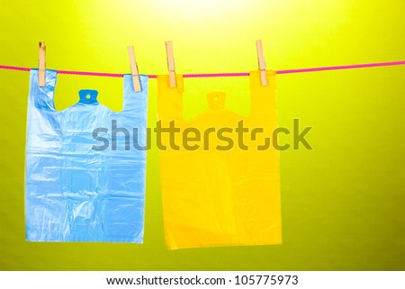 Cellophane bags hanging on rope on green background