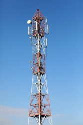 Cellular, mobile phone transmitter tower and weather station with blue sky