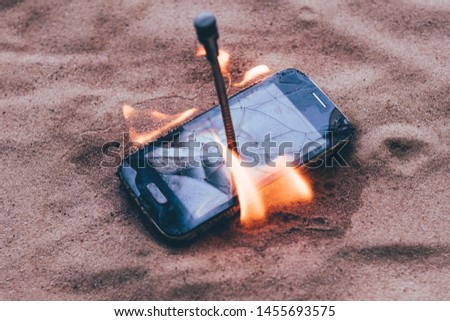 cellular telephone. on the beach sand. it has a metal nail in it. it burns with open fire. #1455693575