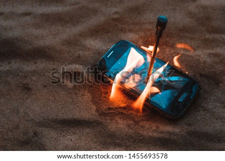 cellular telephone. on the beach sand. it has a metal nail in it. it burns with open fire. #1455693578