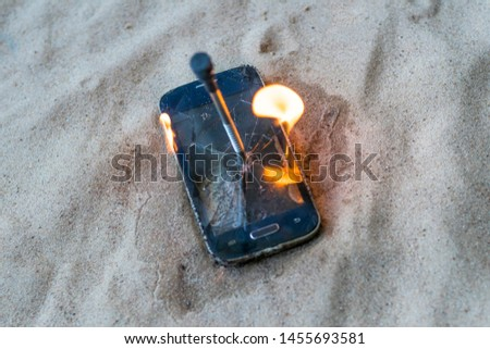 cellular telephone. on the beach sand. it has a metal nail in it. it burns with open fire. #1455693581