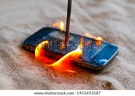 cellular telephone. on the beach sand. it has a metal nail in it. it burns with open fire. #1455693587