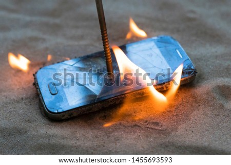 cellular telephone. on the beach sand. it has a metal nail in it. it burns with open fire. #1455693593