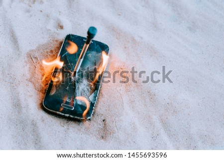 cellular telephone. on the beach sand. it has a metal nail in it. it burns with open fire. #1455693596