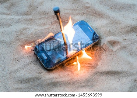 cellular telephone. on the beach sand. it has a metal nail in it. it burns with open fire. #1455693599