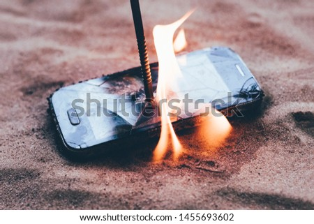 cellular telephone. on the beach sand. it has a metal nail in it. it burns with open fire. #1455693602