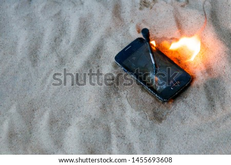 cellular telephone. on the beach sand. it has a metal nail in it. it burns with open fire. #1455693608