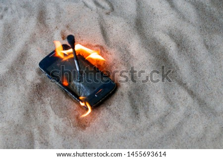 cellular telephone. on the beach sand. it has a metal nail in it. it burns with open fire. #1455693614