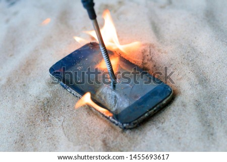 cellular telephone. on the beach sand. it has a metal nail in it. it burns with open fire. #1455693617
