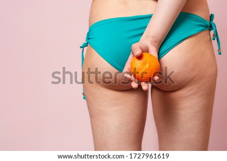 cellulite of a young girl in a blue swimsuit with an orange in her hands . on a pink isolated background Сток-фото ©