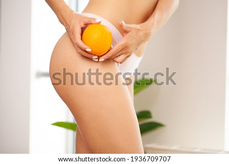 Cellulite problem concept, young woman holding orange near her leg Сток-фото ©