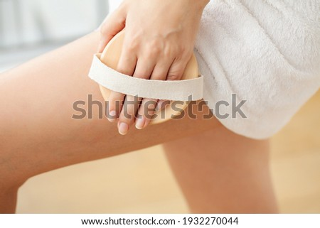 Cellulite treatment, woman arm holding dry brush to of her leg. Foto stock ©