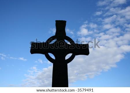 Celtic cross silhouetted against blue sky near Iona Abbey Scotland - stock photo