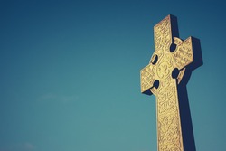 Celtic Cross Stone Gravestone Against Blue Sky With Copy Space