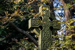 Celtic High Cross surrounded by Autumn foliage in Abney Park Cemetery. The graveyard is one of London's magnificent seven graveyards and now a unique urban wilderness & inner city nature reserve