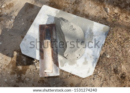 Cement bag and cement trowel at the construction site #1531274240