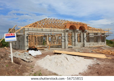 Cement Block home under construction, wood trusses installed. Sold sign in front