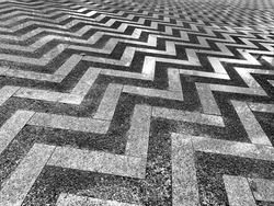 Cement floor decorated with marble with a zigzag pattern.