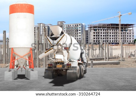 Cement mixer truck parked in front of a new building under construction with precast concrete piles