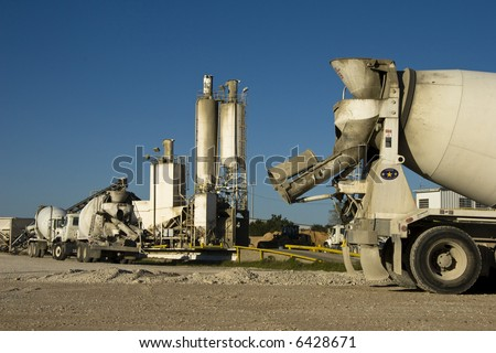 Cement mixer truck with plant in background