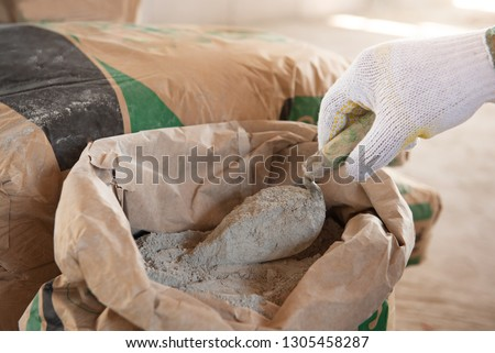 Cement or cement mortar with a trowel placed on a cement bag for construction work. #1305458287