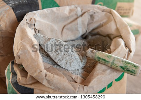 Cement or cement mortar with a trowel placed on a cement bag for construction work. #1305458290