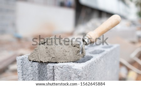 Cement or cement mortar with a trowel placed on the brick for construction work. #1562645884