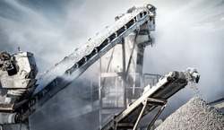 Cement production factory on mining quarry. Conveyor belt of heavy machinery loads stones and gravel