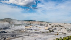 Cement production factory on mining quarry. Stone crushing equipment, working conveyor loading gravel and producing air pollution with dust and smog