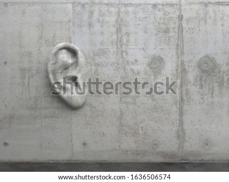 """Cement sculpture in the shape of a human ear on a concrete wall. Illustration of the metaphor """"Even walls have ears."""" Creative conceptual modern art with copy space. 3D rendering"""
