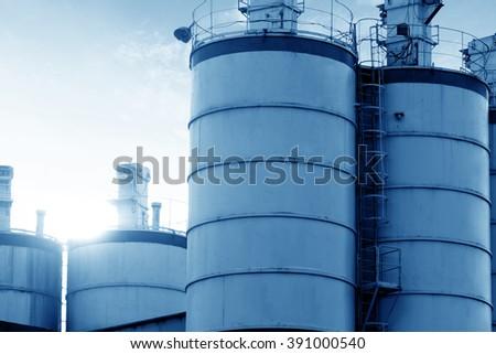 Cement silo under backlit, blue tone image.