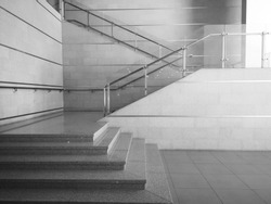 Cement staircase with steel railings in the building. Stairway up the building with glass partition.
