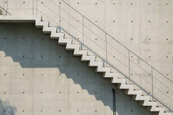 Cement stairs in outside the high modern building with handrails and sunlight shadow