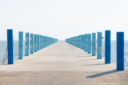 Cement walkway / path with pillar, post, pole in pastel color stretch into the sea