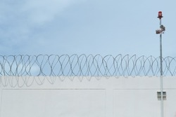 Cement wall of prison with barbwire and alarm horn pole