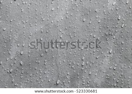 Cement wall texture background with water droplets and hairline cracks close up