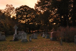 Cemetary during an orange sunset in the summer.